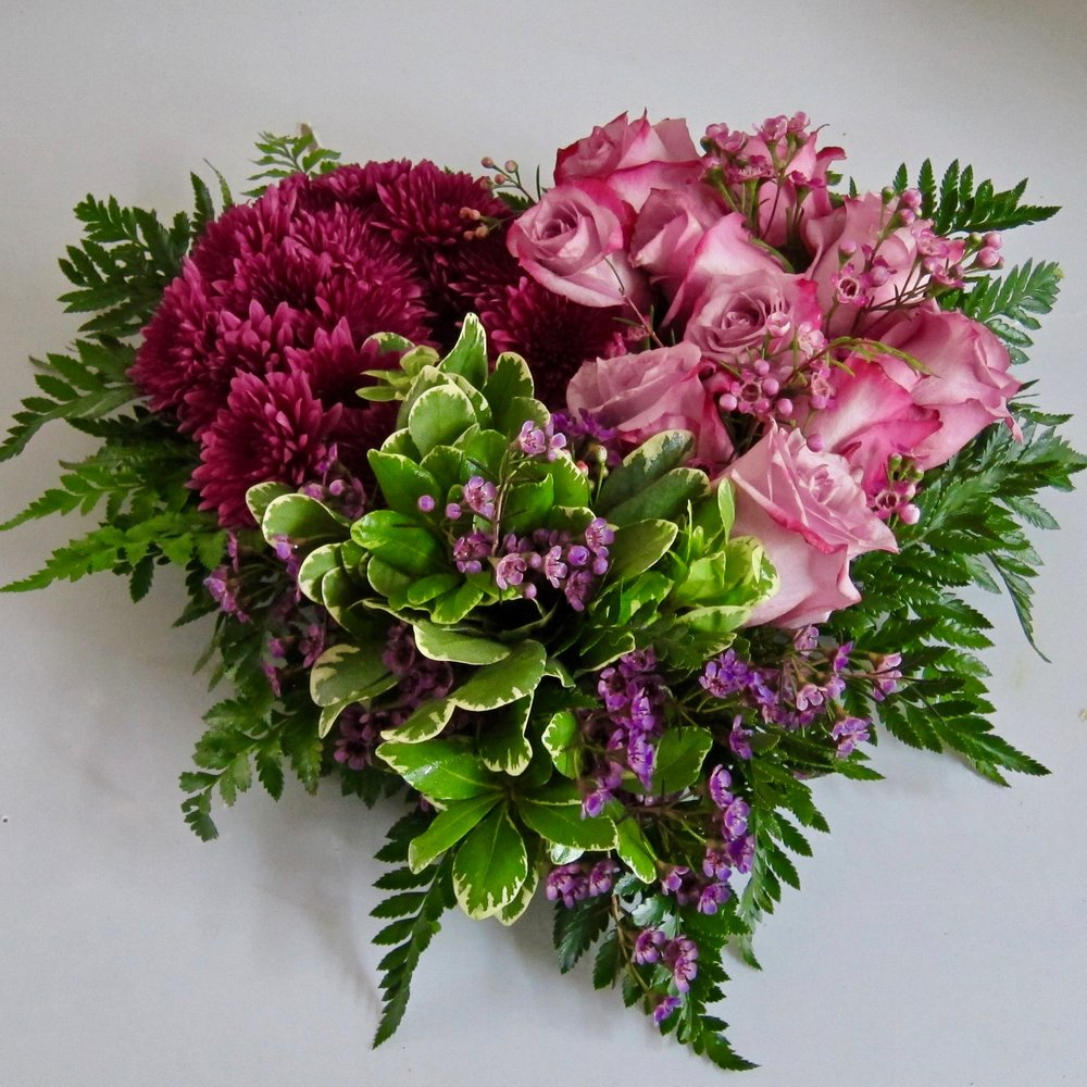 MY HEART SPEAKS TO YOU   Roses and mums with lush foliage and fragrant waxflower lies flat on a tabletop, $99.