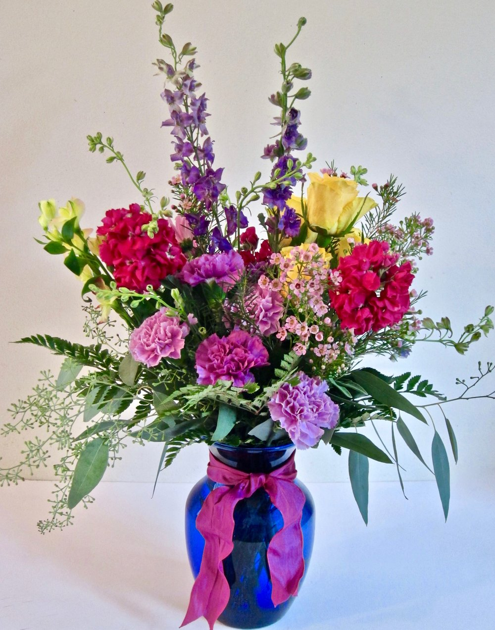 RAYS OF ROMANCE   Purples and yellows in a 7 inch rose vase, $45.