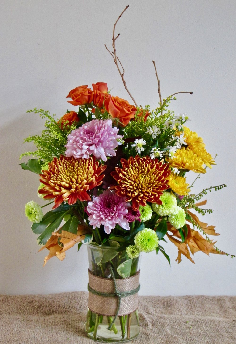 BURLAP WRAP   Copper, bronze and purple flowers with fall foliages in a burlap wrapped vase, $45.