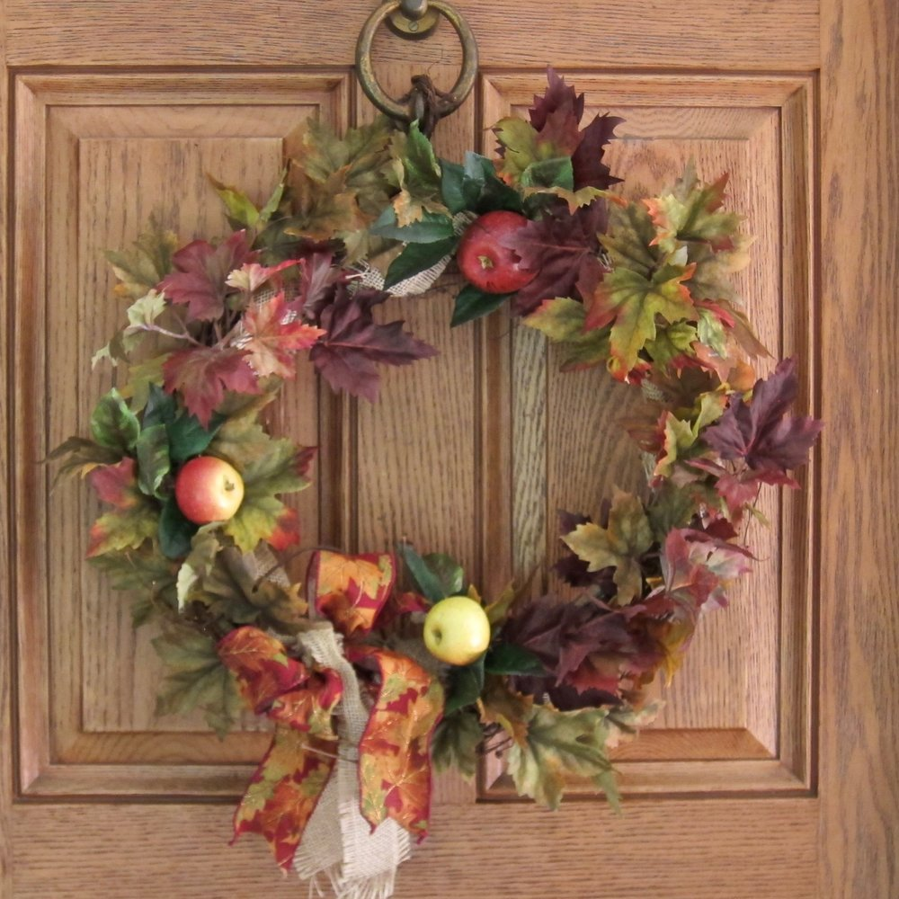 PERMANENT SILK LEAF WREATH   Apples and leaves on a grapevine form with a designer bow. Makes a unique and long-lasting gift.   Advance notice needed.