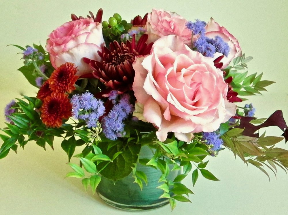 LEAF-LINED CYLINDER   Fall colors of roses and mums with seasonal accents, $50.
