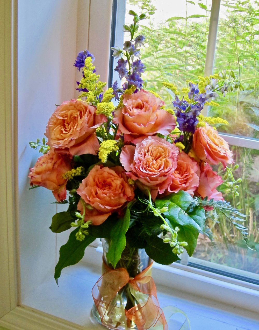 CLASSIC DOZEN ROSES   Twelve roses accented with foliage and fillers, $75. Shown here, our signature Free Spirit Rose with purple larkspur and yellow solidago..