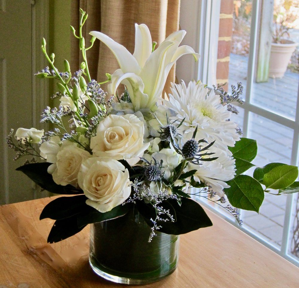 LOW AND LACY PREMIUM WHITE FLOWERS, hydrangea, roses, cremons, lily, highlighted with soft misty in a leaf-lined cylinder, $55 to $65.