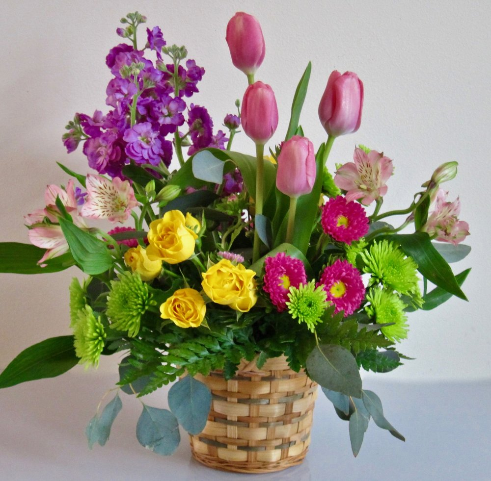 """SMALL BASKET ARRANGEMENT   Seasonal flowers in a five inch basket (or ceramic vase), about 12"""" wide by 15"""" high., $55."""