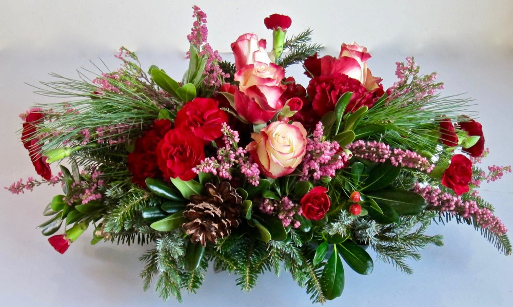 SMALL LOW CENTERPIECE OF seasonal greens, roses and carnations with accents of cones and berries, $40.
