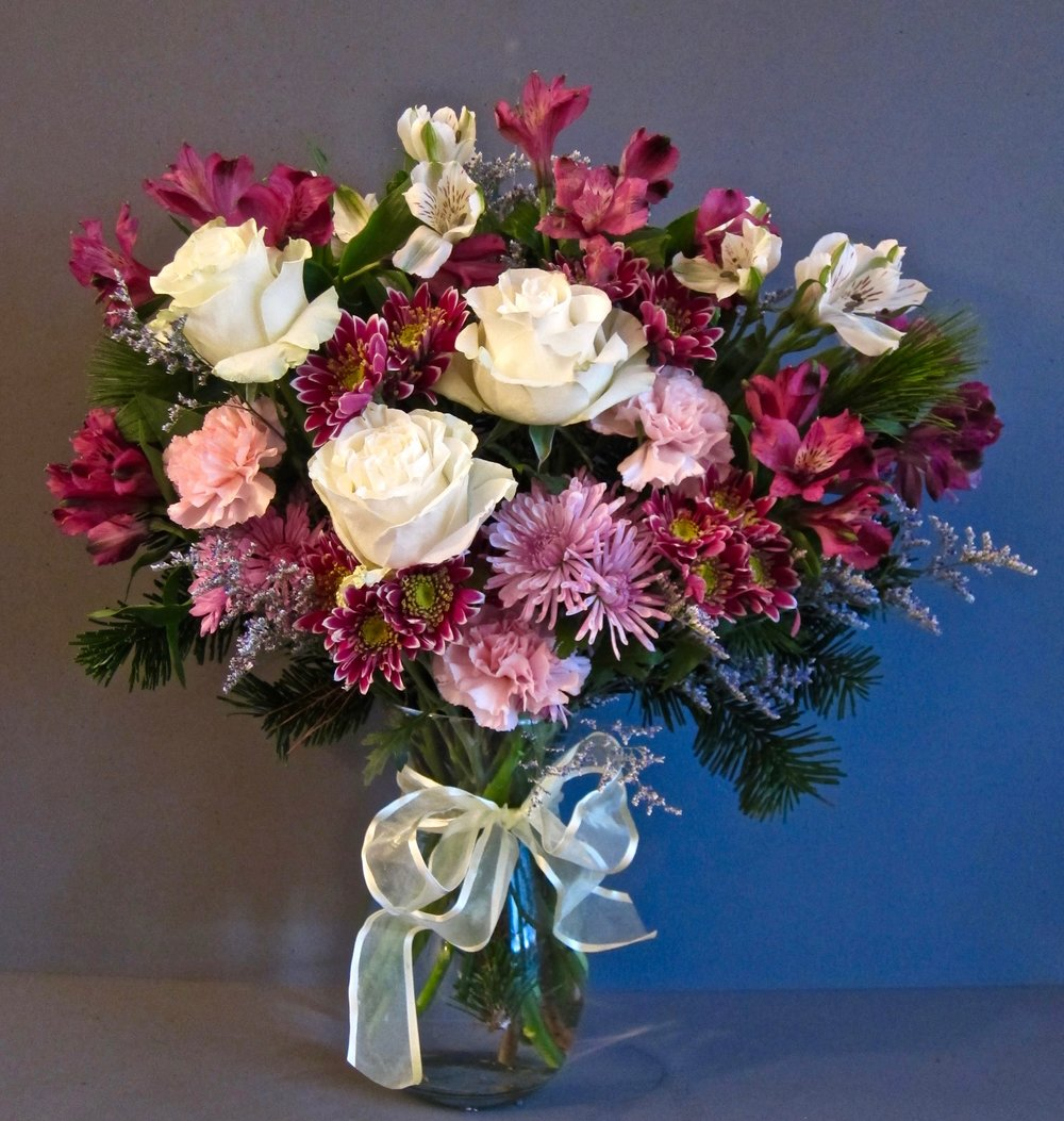 LARGE STANDARD MIX, mums, alstro, carnations, roses with seasonal greens in 10 inch vase, $65. Small 8 inch rose vase, $40.