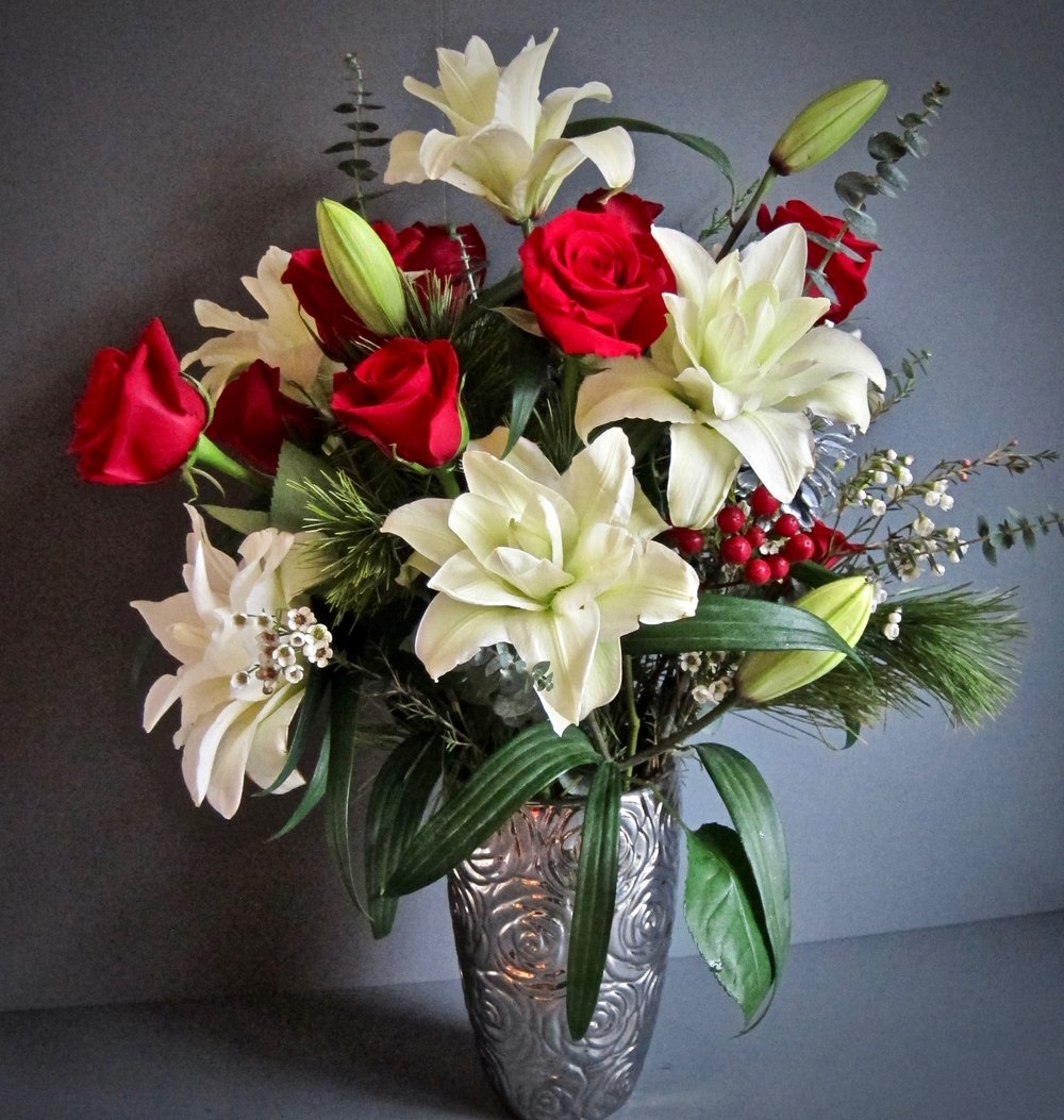 WINTER LILIES AND ROSES with seasonal greens and accents, $75.