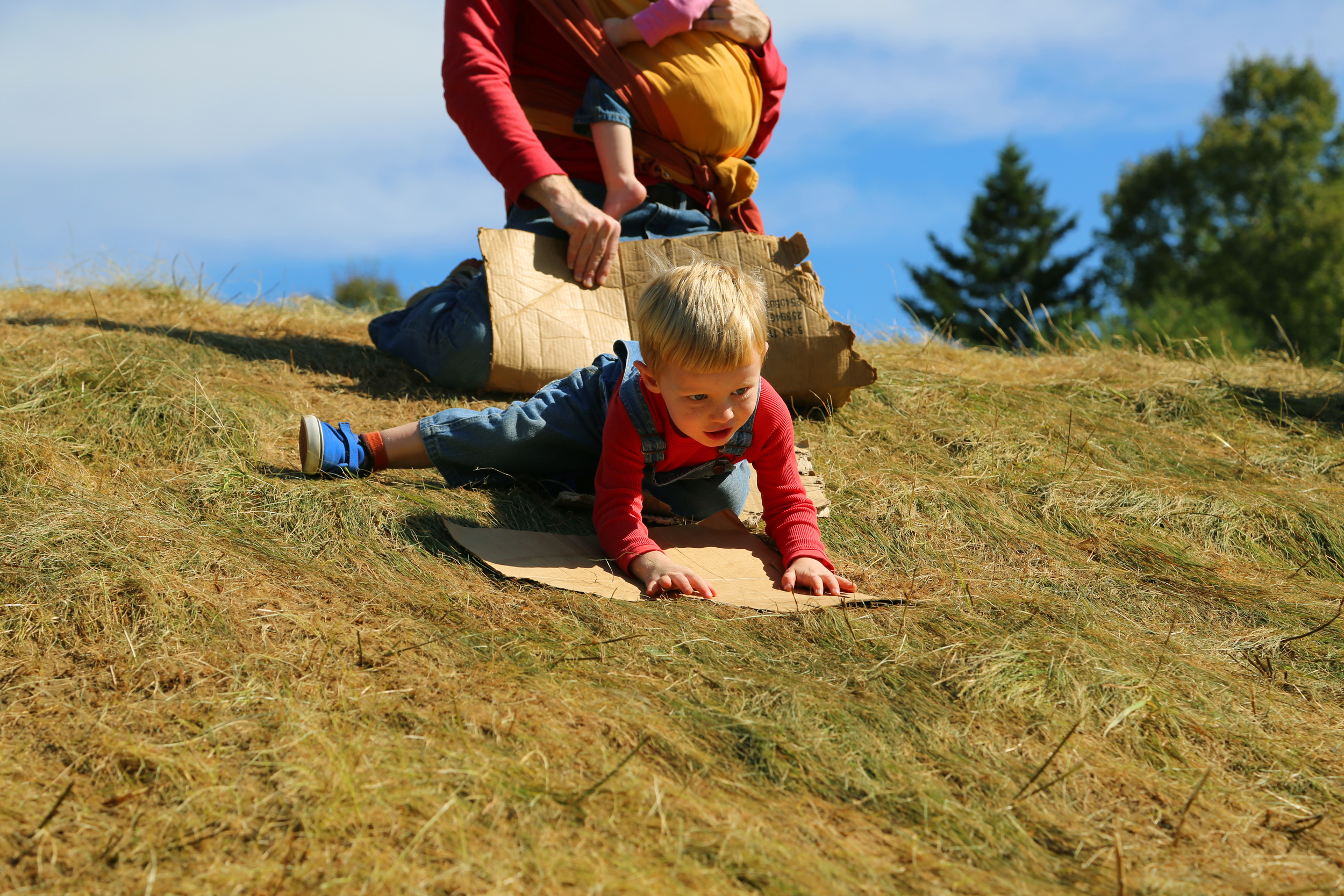 This desert kid was excited to slide down the grassy hill on his magic carpet.