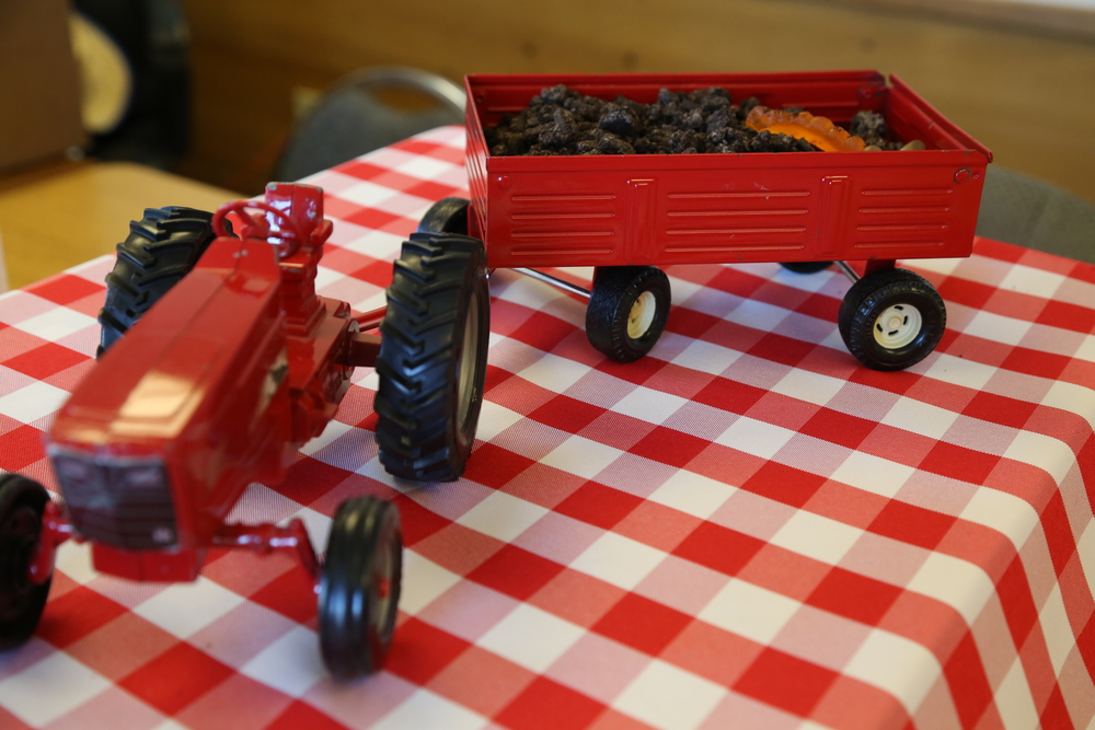 "The ""cake!""  This is Geoff's old tractor.  In the trailer is a big brownie topped with Oreo crumbs and worms.  The guests had Oreo pudding cups I made and topped with Oreo crumbs and gummy worms."