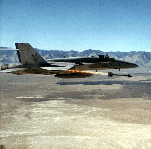 F/A-18 Hornet firing AIM-9 Sidewinder; China Lake's mission-avionics efforts have ranged from electromechanical bomb directors to software-intensive hybrid systems, integrated targeting/nav/EW suites, training devices, and operational flight programs (OFPs).