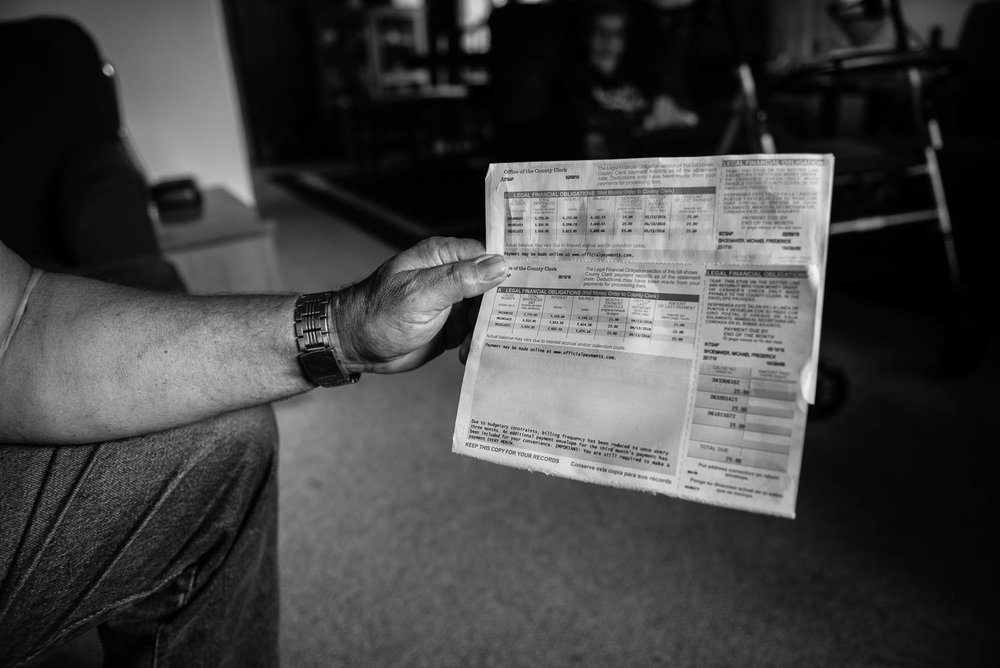 "Michael displays the invoice he receives from the county court, showing the $17,000 he owes in LFOs. ""I'll be dead before that's paid off."" The invoice also shows that all of his monthly payments have thus far been applied to the interest only."