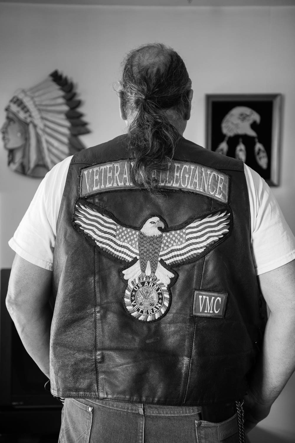 Wearing his motorcycle vest, Michael stands before two wood carvings that his father had made. Michael's father has passed away.