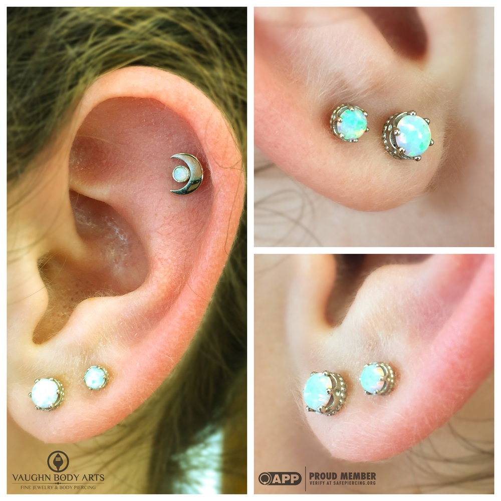 "Earlobe piercings with 18k white gold ""Queen"" ends, and helix piercing with 18k gold moon end from Anatometal."