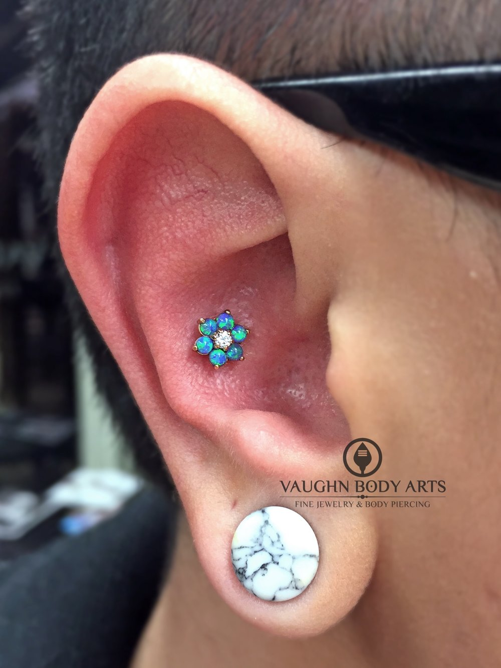 Conch piercing featuring an 18k yellow gold flower from Anatometal.