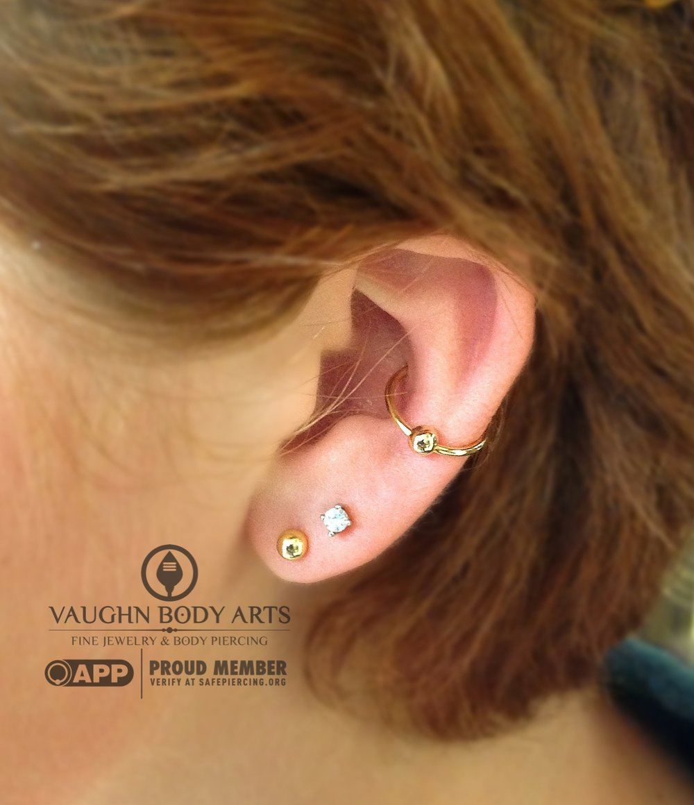 Conch piercing with an 18k yellow gold fixed bead ring from Anatometal.