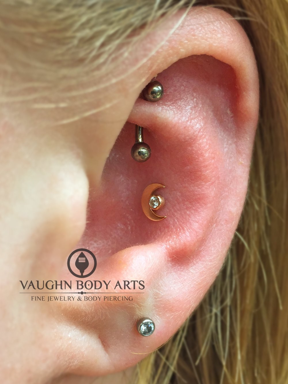 Conch piercing with an 18k yellow gold and cz crescent moon end from Anatometal.