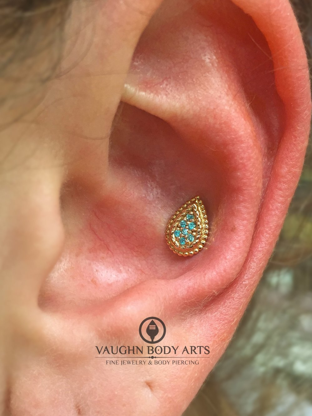 "Conch piercing featuring a 14k yellow gold ""Kendra"" end with mint green cz's from BVLA."