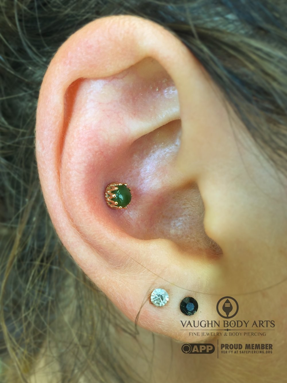 "Conch piercing with an 18k yellow gold ""King"" end featuring genuine Jade from Anatometal."