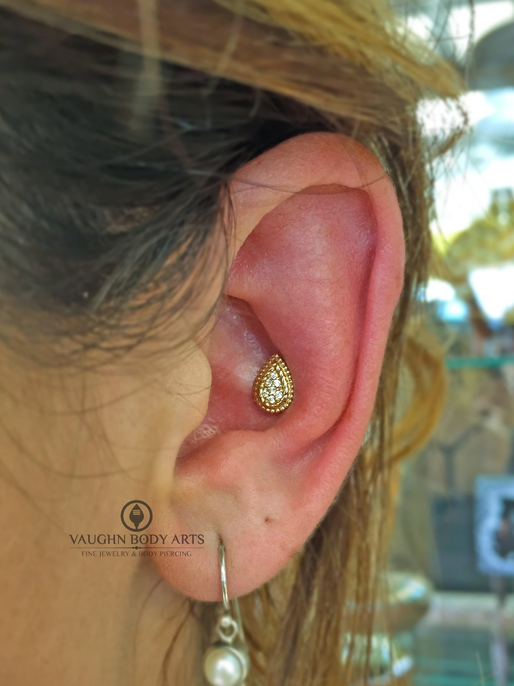 "Conch piercing featuring a 14k yellow gold and clear cz ""Kendra"" end from BVLA."