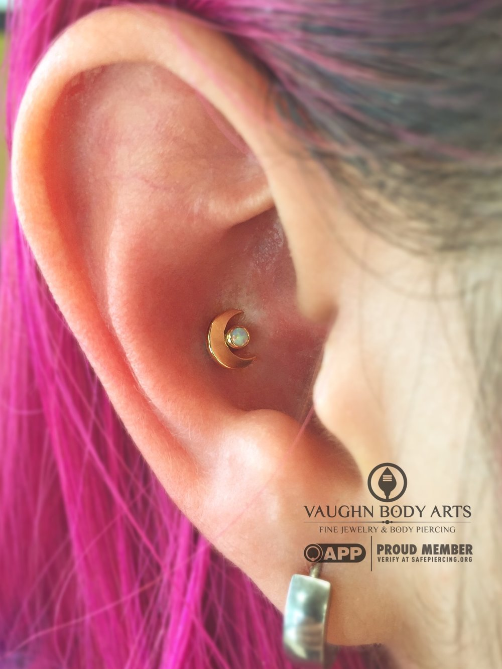Conch piercing with an 18k yellow gold and opal crescent moon from Anatometal.