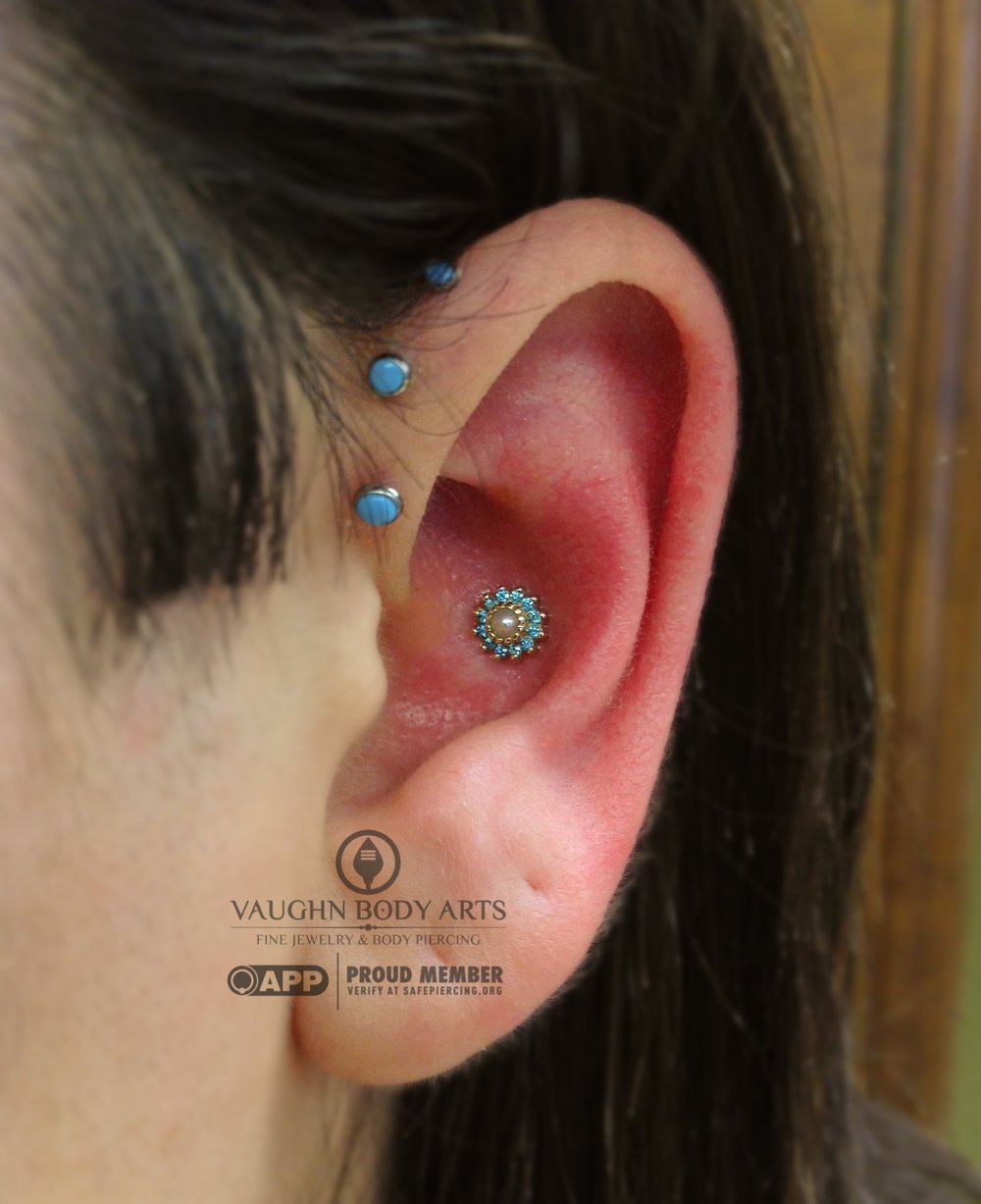 "Conch piercing with a 14k yellow gold ""Rose"" end featuring mint green cz's and a genuine pearl from BVLA."