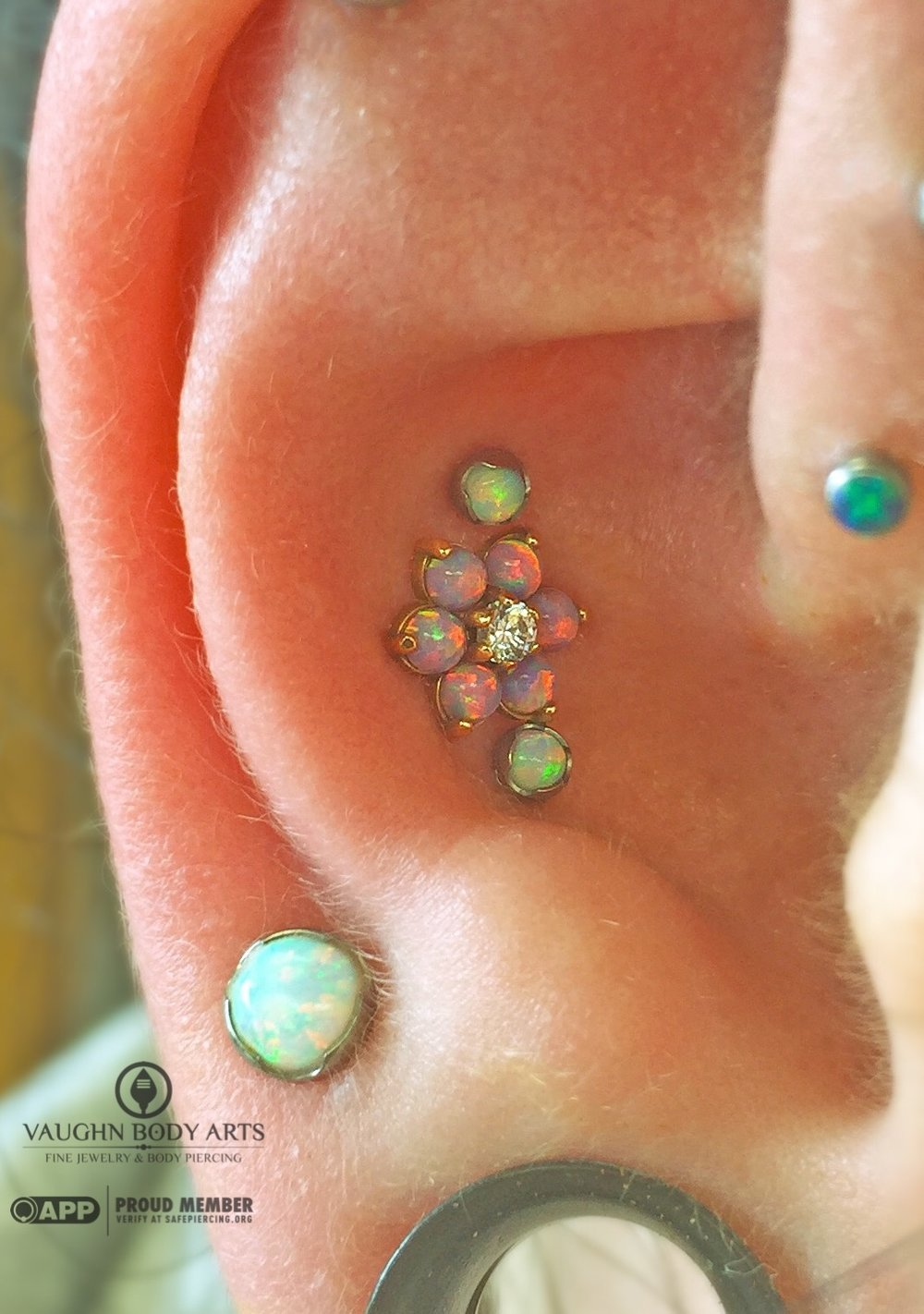 Triple conch piercings featuring jewelry from Anatometal. 18k rose gold flower with light purple opals and two little white opals for accents.