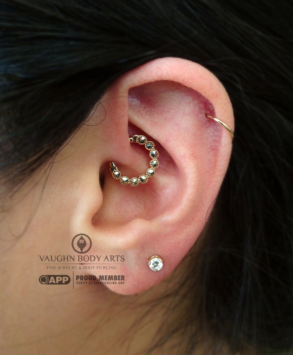 "Daith piercing featuring a 14k yellow gold and genuine marcasite ""Marina"" hinged ring from BVLA."