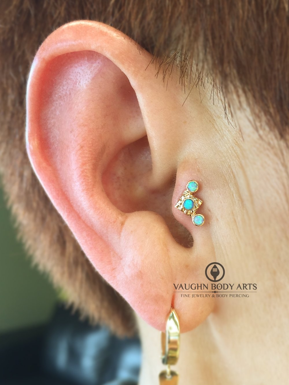 "Tragus piercing featuring an 18k yellow gold and opal ""Kira Cluster"" end from Anatometal."