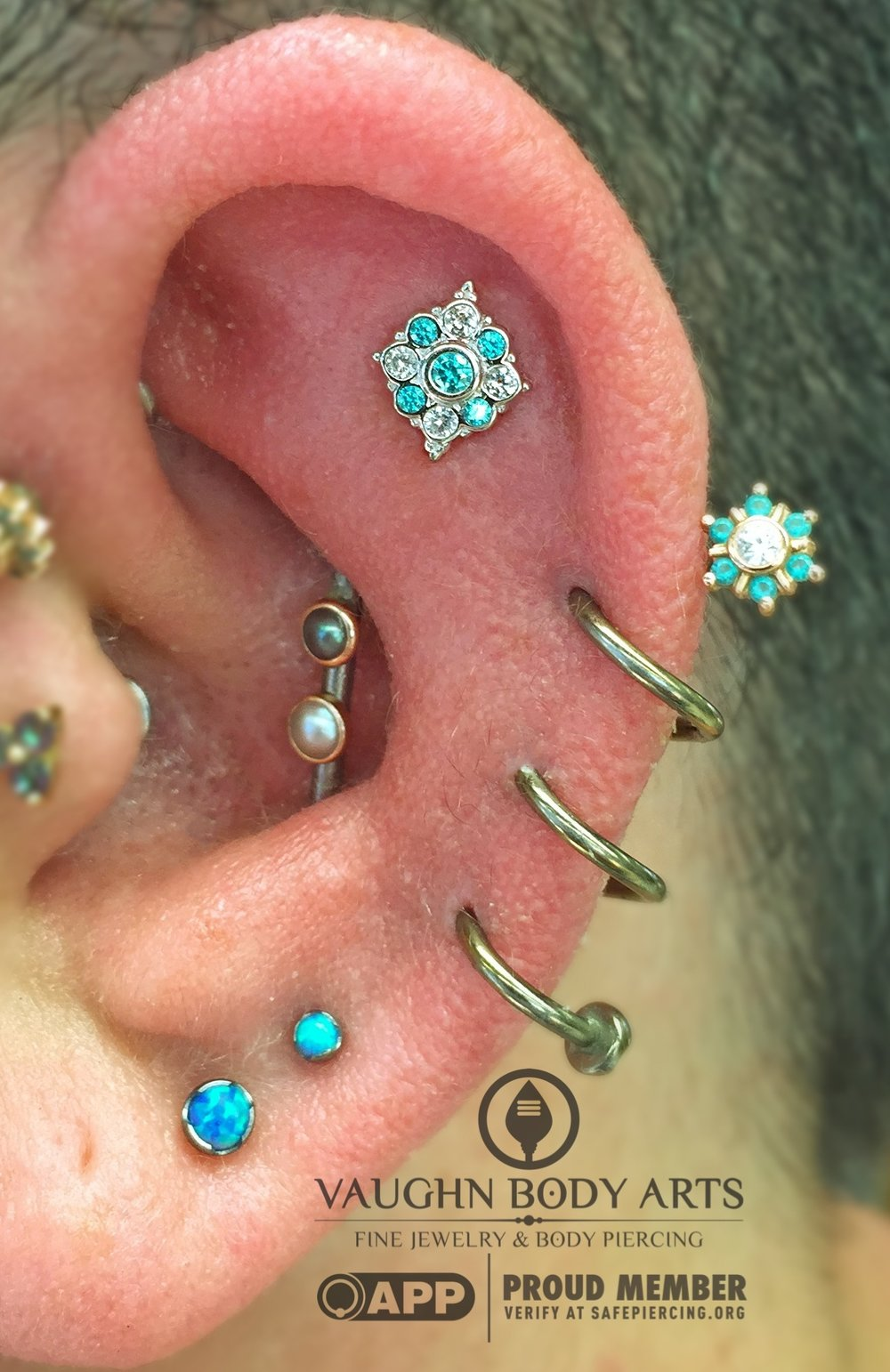 "Helix piercing featuring a 14k white gold ""Angela"" end with mint green cz's and white sapphires from BVLA."