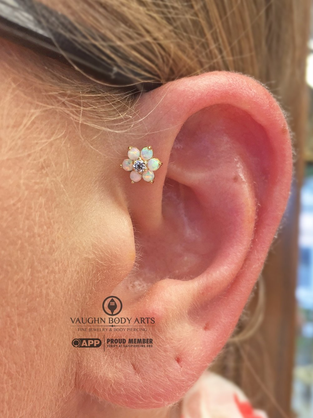 Forward helix piercing with 18k yellow gold flower from Anatometal.
