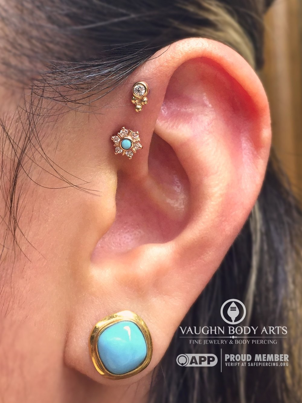 "Double forward helix piercings with an 18k yellow gold ""Sabrina"" end from Anatometal on top, and a 14k yellow gold ""Toltec"" with turquoise and clear cz's from BVLA on the bottom."