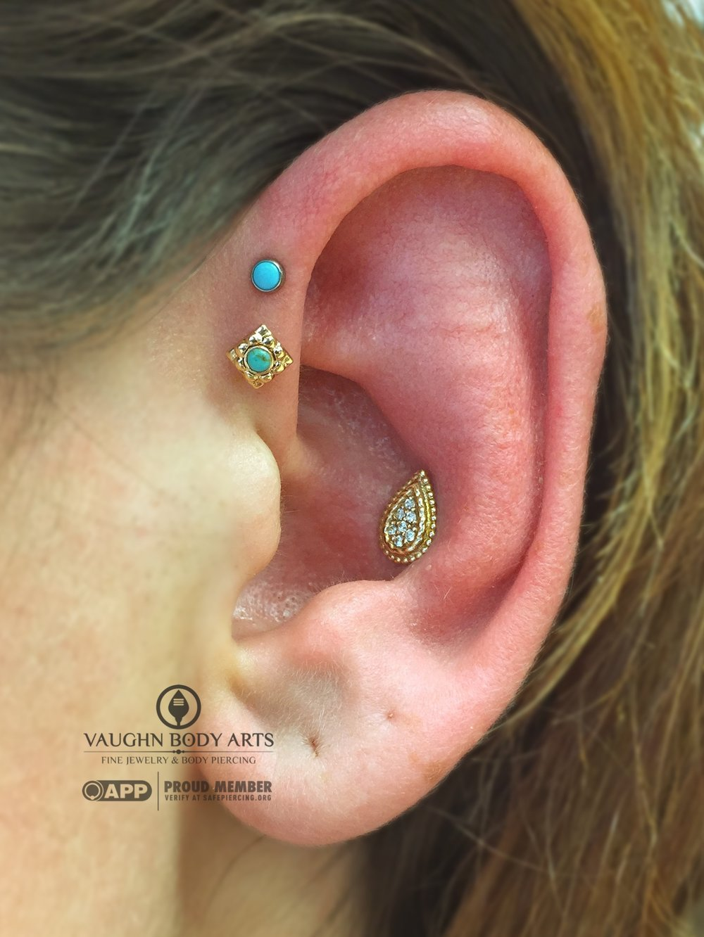 "Double forward helix piercing with an 18k yellow gold ""Kira"" end from Anatometal and titanium jewelry from NeoMetal. Conch piercing with a 14k yellow gold and cz ""Kendra"" end from BVLA."