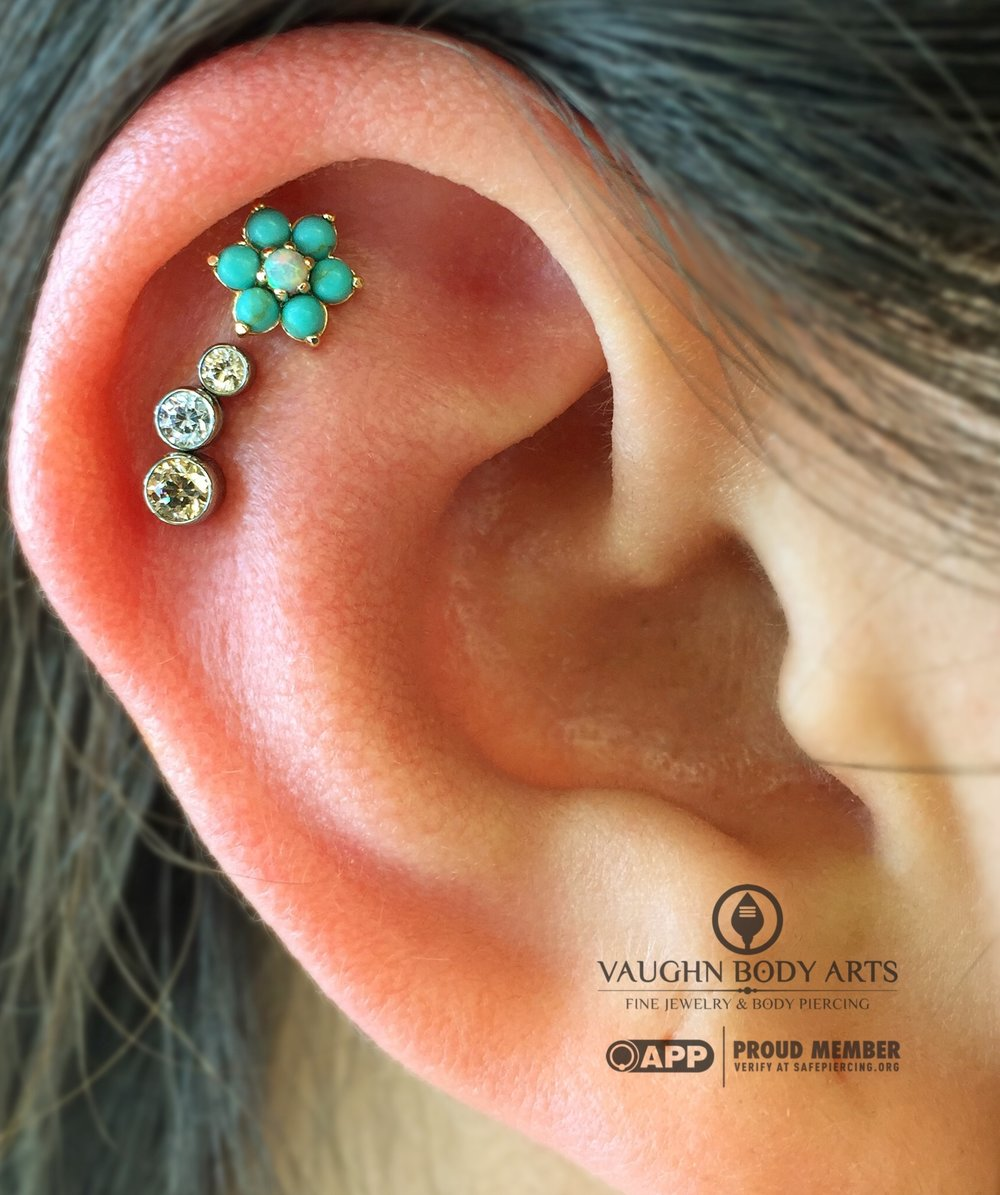 Helix piercings with an 18 yellow gold flower and titanium gem cluster from Anatometal.