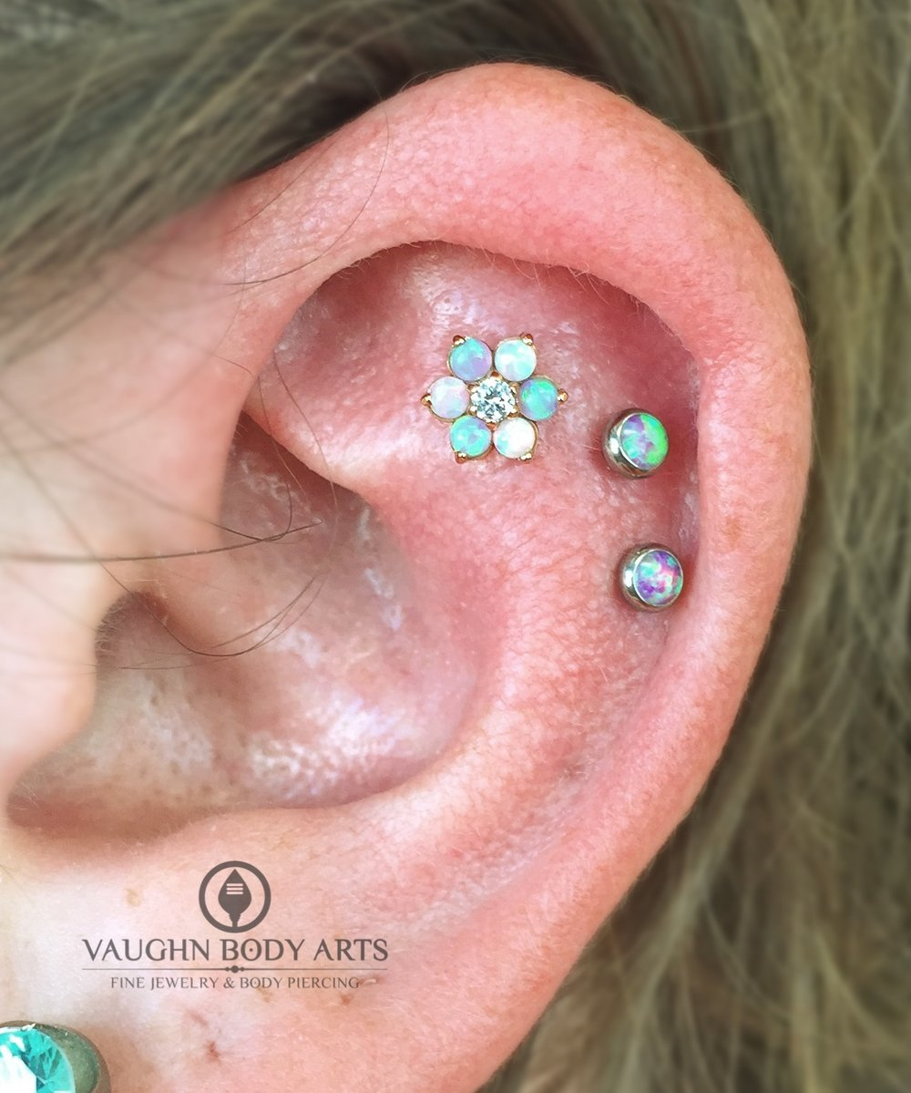 Helix piercings with an 18k yellow gold flower and titanium jewelry from Anatometal.