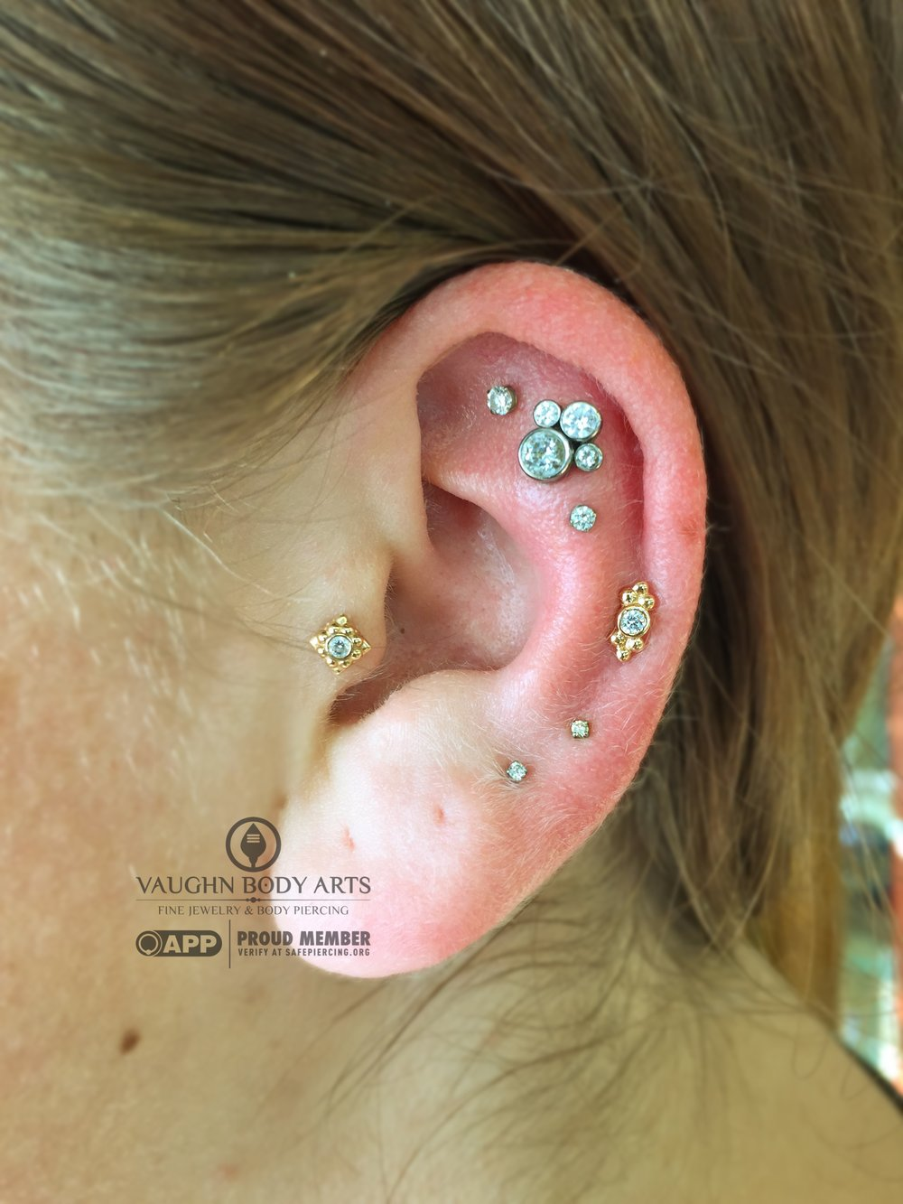 "Tragus piercing with an 18k yellow gold and cz ""Kira"" end, helix with an 18k yellow gold and cz ""Sabrina"" end from Anatometal."