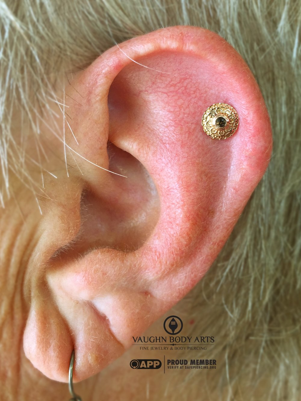 "Helix piercing featuring a 14k yellow gold ""Nanda"" end with genuine smokey quartz from BVLA."