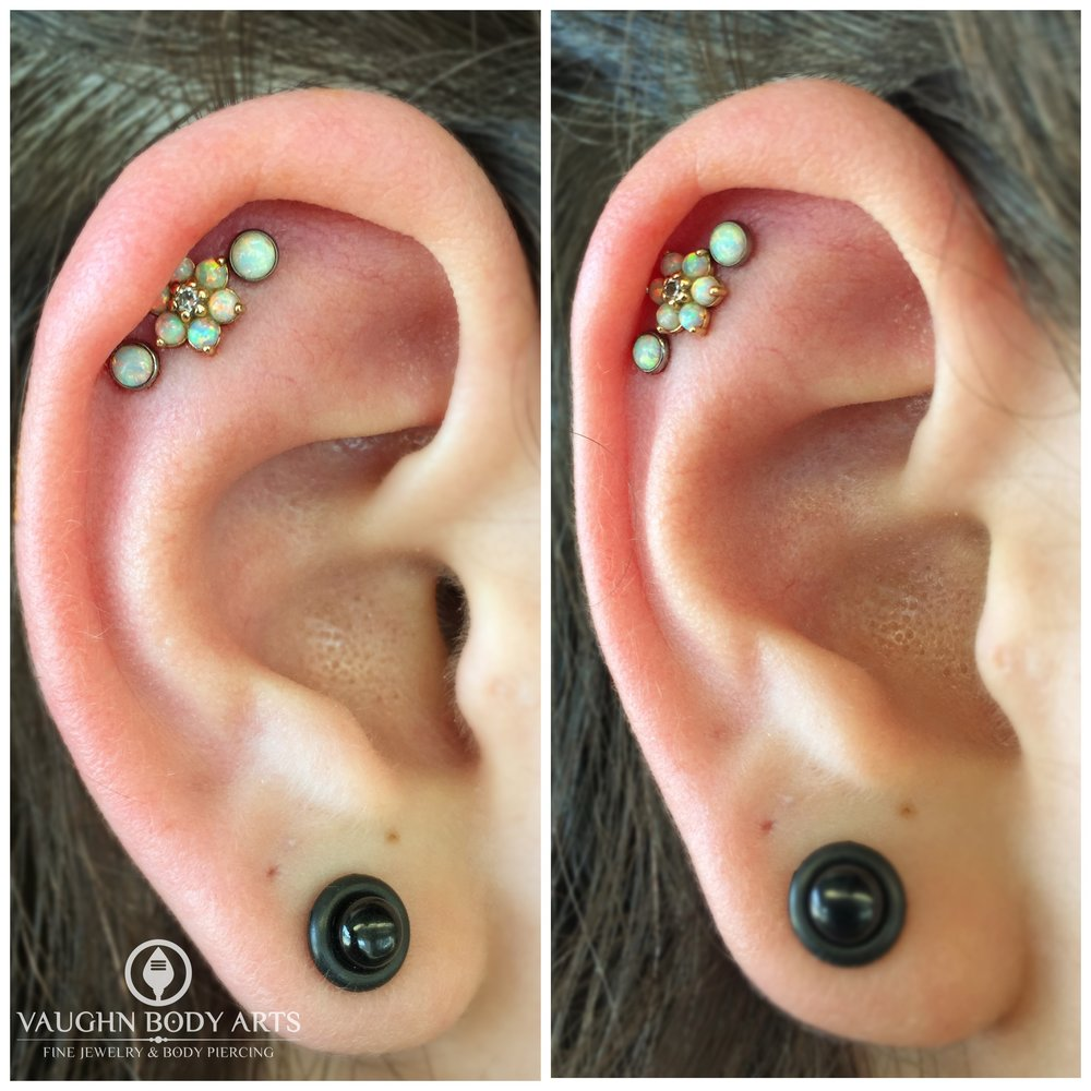 Triple helix piercings with titanium jewelry from Anatometal featuring an 18k yellow gold flower in the center.