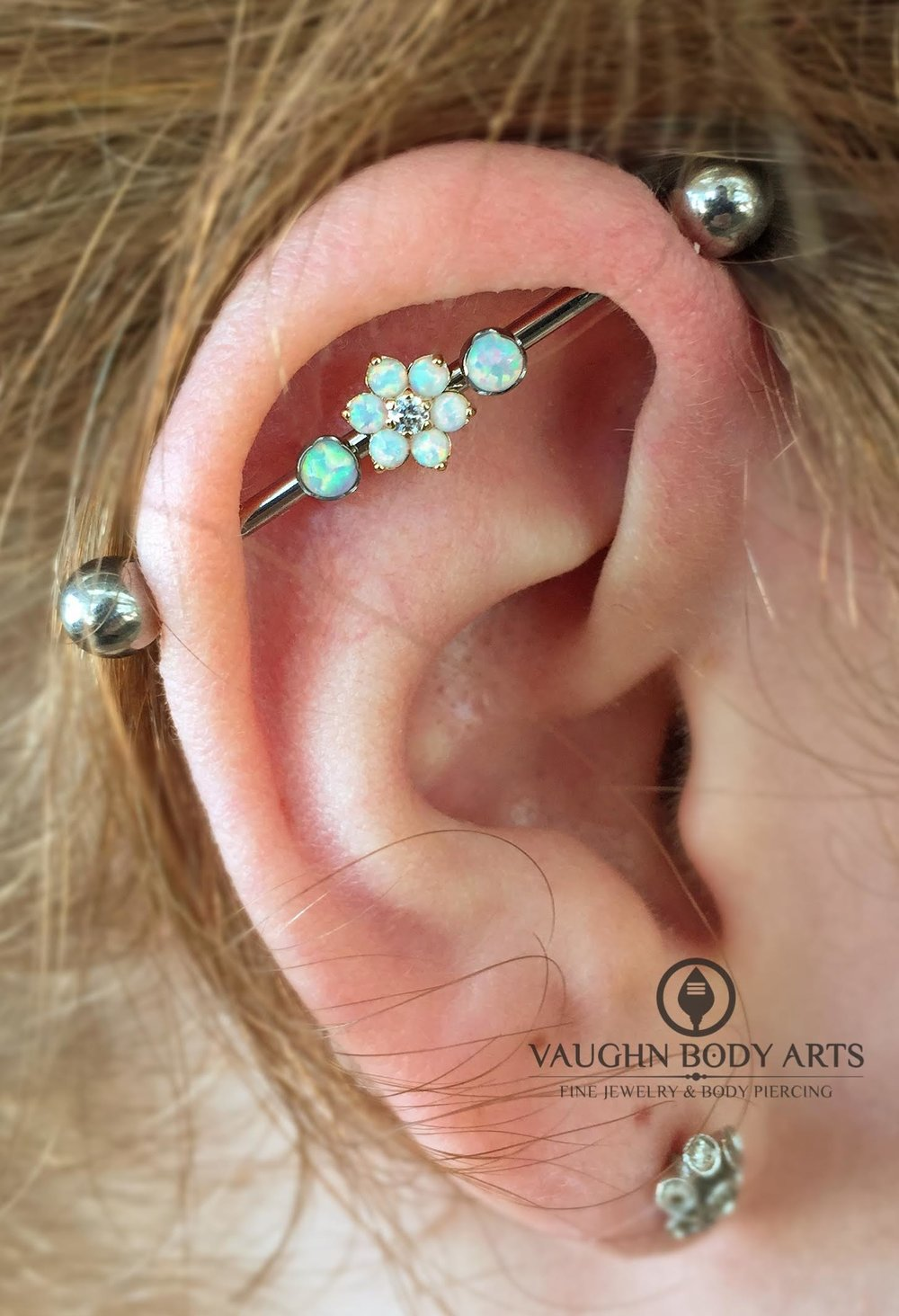 Industrial piercing with titanium jewelry from Anatometal featuring an 18k yellow gold flower in the center.