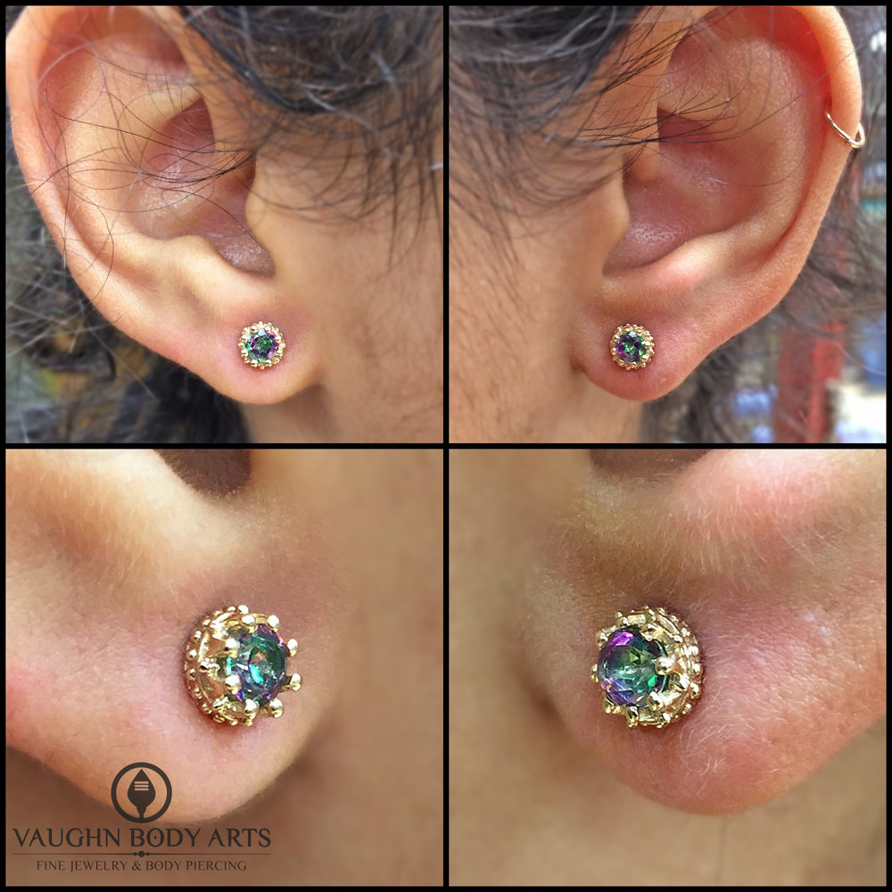 "Earlobe piercings with 14k yellow gold ""Crown"" ends featuring mystic topaz from BVLA."