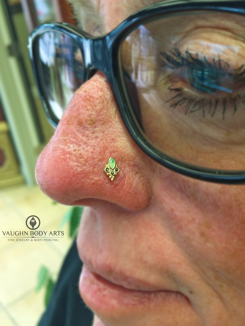 "Nostril piercing with a 14k yellow gold ""Marquise Sarai"" end with chrysoprase and genuine black diamonds from BVLA."