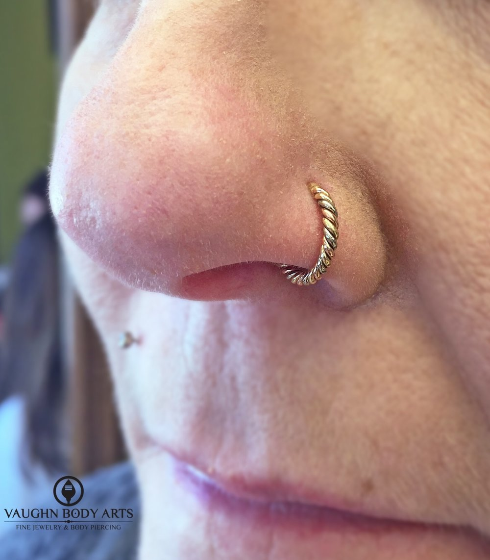 "Nostril piercing with a 14k tri-tone ""Desiree"" ring from BVLA, mixing yellow, rose, and white gold."