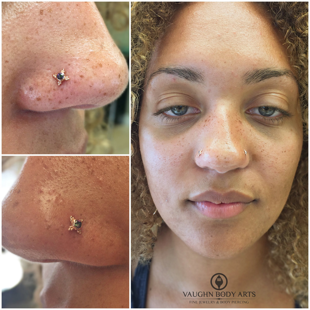 "Paired nostril piercings featuring 14k rose gold ""Mini Kandy"" ends with mystic topaz from BVLA. Her right nostril was not pierced by us."