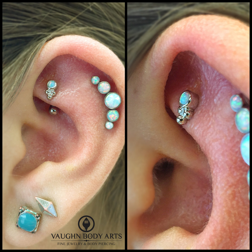 "Rook piercing with an 18k white gold and opal ""Sabrina"" end, and helix piercing with a titanium gem cluster from Anatometal."