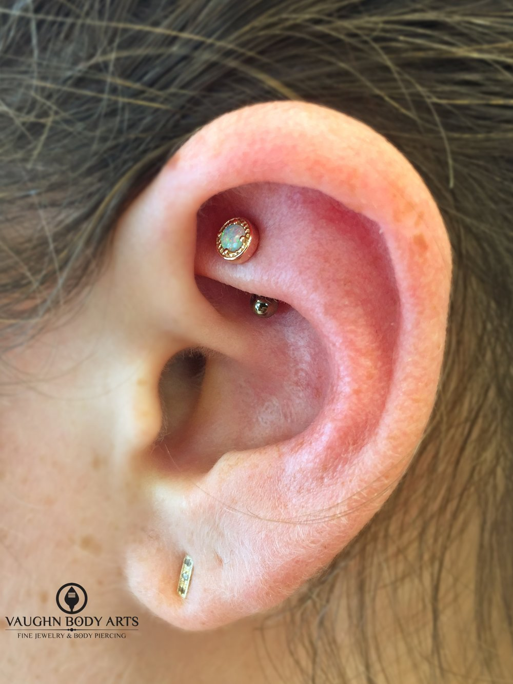 "Rook piercing with a 14k yellow gold and opal ""Millgrain Prong"" end from BVLA."