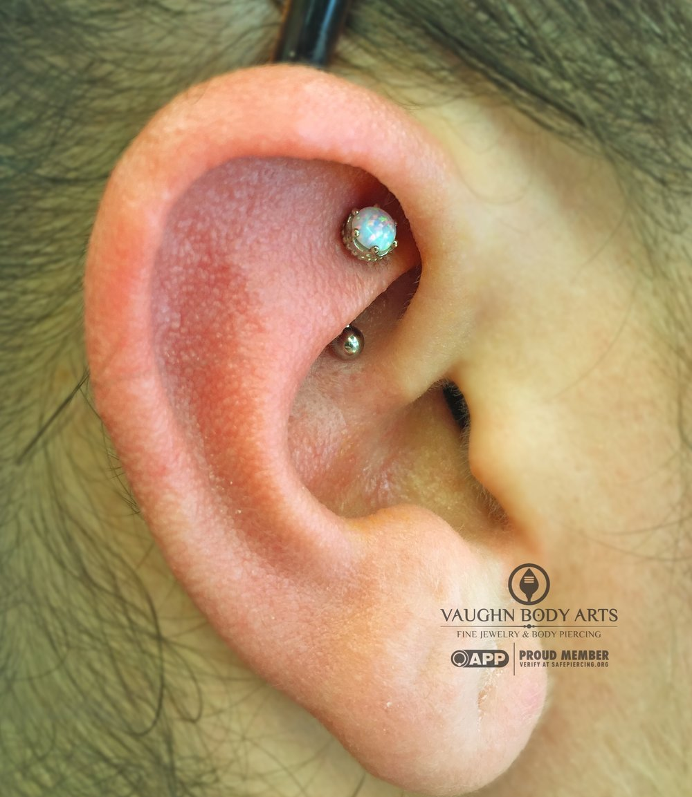 "Rook piercing with an 18k white gold and opal ""Queen"" end from Anatometal."