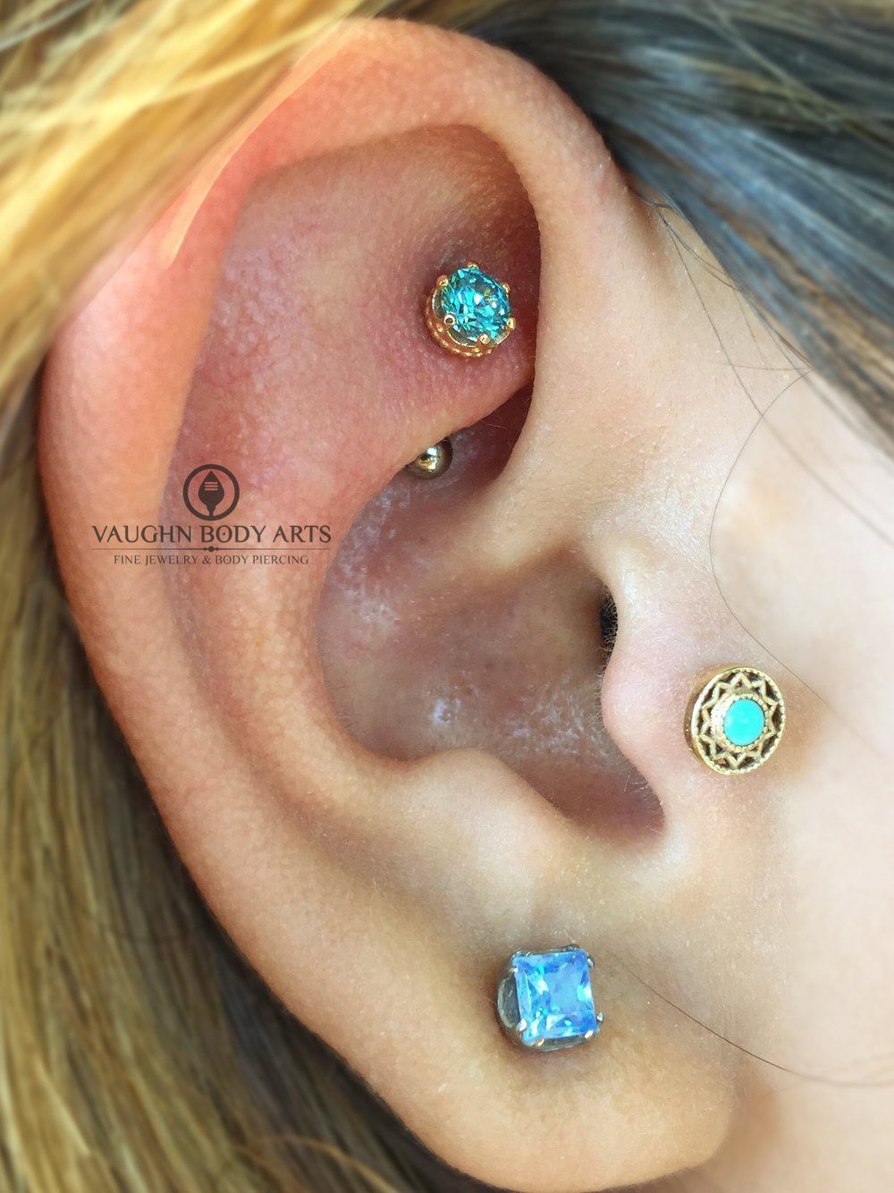 "Rook piercing with an 18k rose gold and mint green cz ""Queen"" end from Anatometal."
