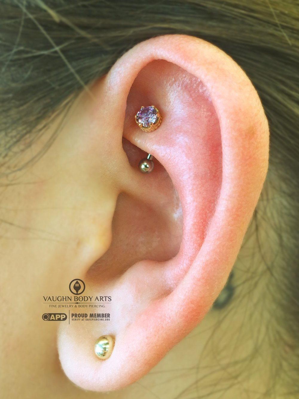 "Rook piercing with an 18k rose gold and amethyst ""Queen"" end from Anatometal."