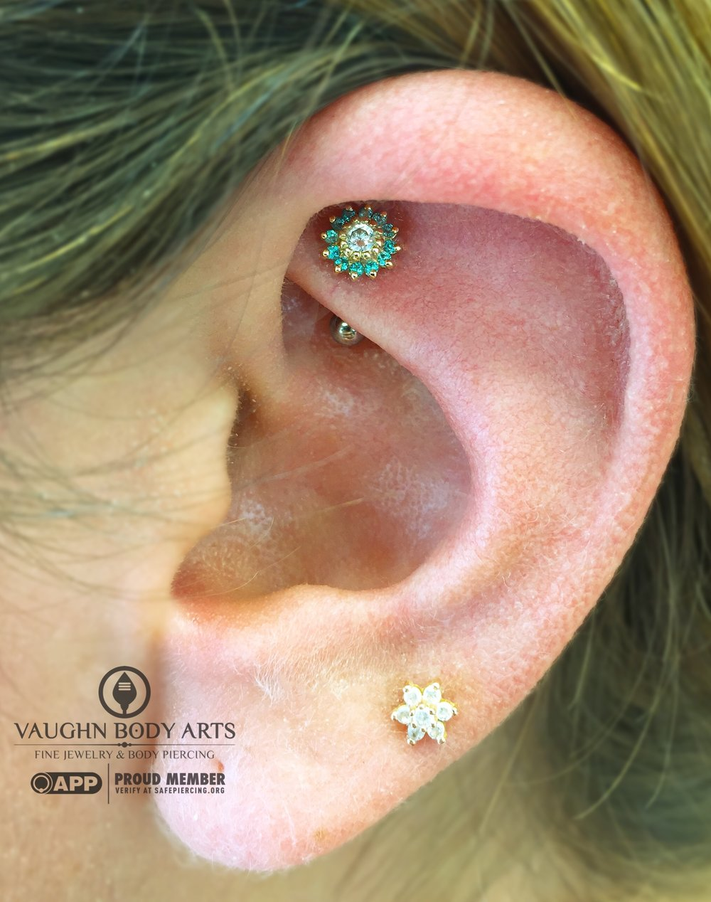 "Rook piercing with a 14k yellow gold ""Rose"" end featuring mint green and clear cz's from BVLA."