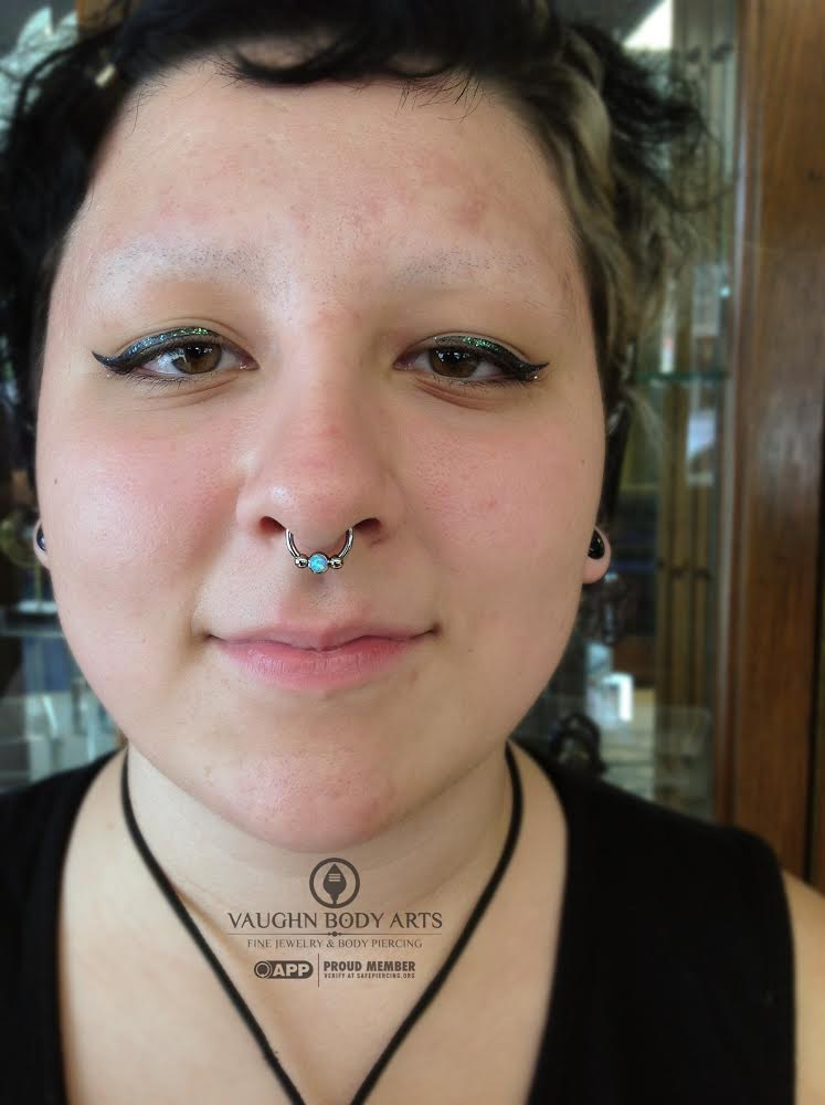 Septum piercing with a titanium circular barbell and opal captive bead from Anatometal.