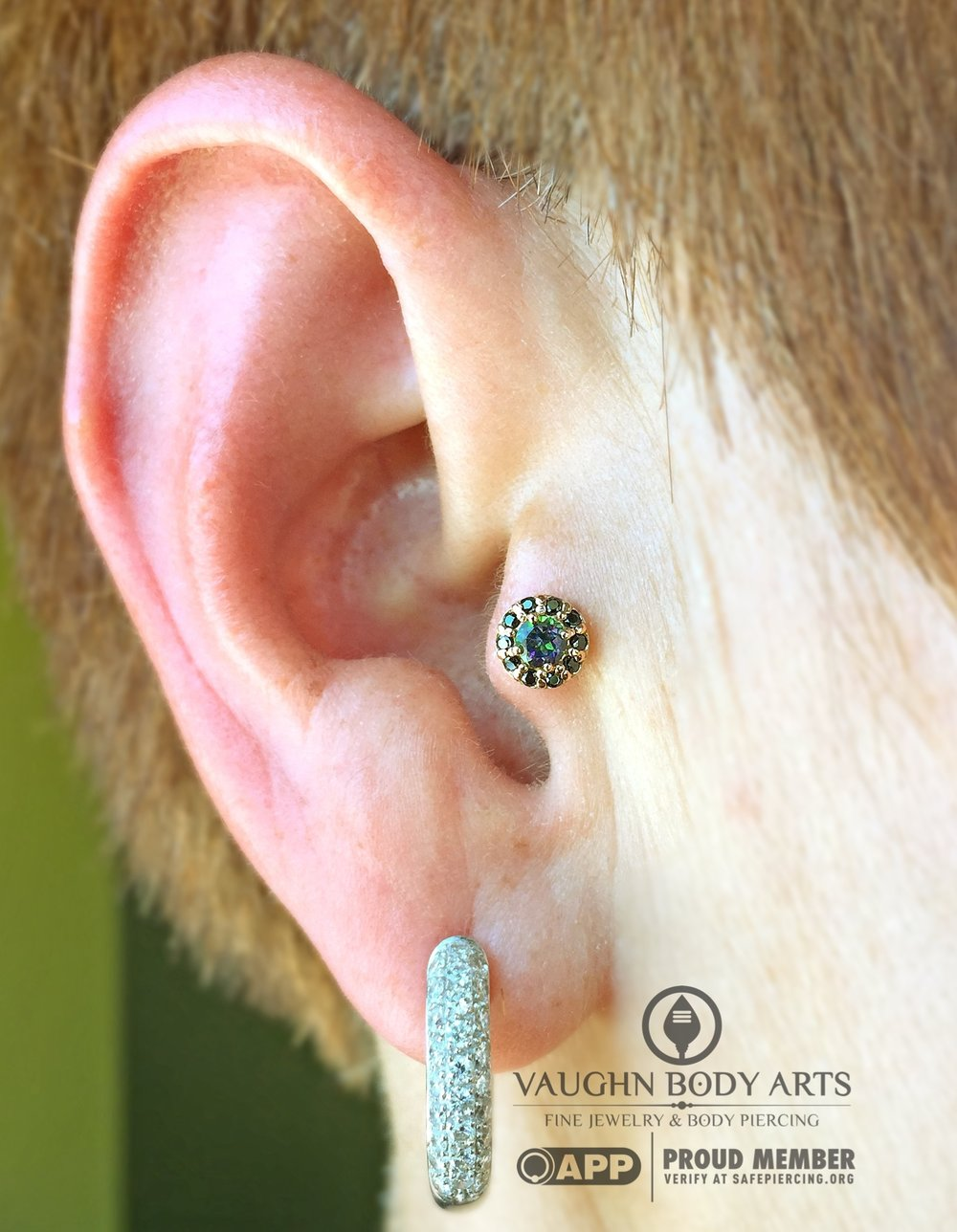 "Tragus piercing featuring a 14k rose gold ""Altura"" end with mystic topaz and black cz's from BVLA."